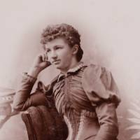 Antique photograph of young woman reclining in chair resting face in hand wearing 19th century style dress